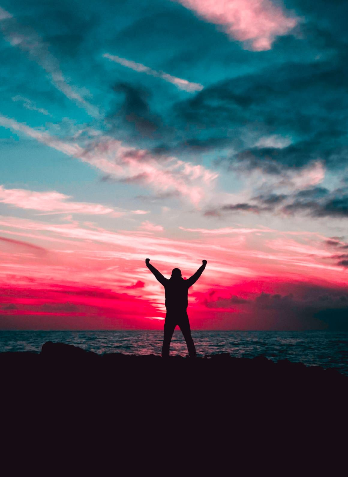 silhouette of man raising hands against a red sunset light 801885 scaled e1585502638248